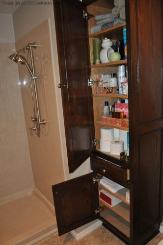 A Bathroom with Staron Countertop Shower with Bench Seat Custom Dark Oak Cabinetry Vinyl Flooring (21) lg