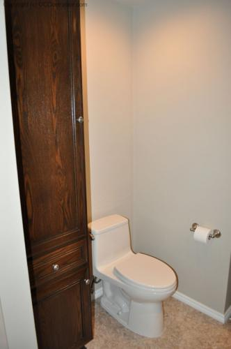A Bathroom with Staron Countertop Shower with Bench Seat Custom Dark Oak Cabinetry Vinyl Flooring (22) lg